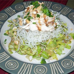 Chinese Chicken Salad Recipe - Delicate rice vinegar dresses this salad of chicken, lettuce, nuts and the requisite sesame seeds and crisp Chinese noodles.