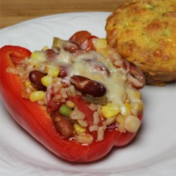 Quick and Easy Stuffed Peppers Recipe - We love that word - easy. The peppers pre-cook in the microwave while you make the tomato, bean, corn, and green onion stuffing. When both are ready, stuff the peppers, and pop in the microwave again. Top with cheese. Easy!