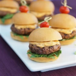 Tomato-Basil Sliders Recipe - Arugula and grape tomatoes augment the flavour of these grilled burgers, perfect for summertime entertaining or quick family meals.