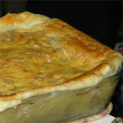Meat Pie, Southern Version Recipe - Topped with flaky puff pastry, this golden brown pie is stuffed with a filling of seasoned ground beef and pork, diced vegetables, and shredded Cheddar cheese.