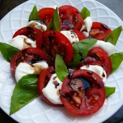 Caprese Salad with Balsamic Reduction Recipe and Video - The lovely Italian salad of sliced tomato, mozzarella cheese, and fresh basil leaves gets a drizzle of sweet, tangy balsamic vinegar reduction for a gourmet summer treat.