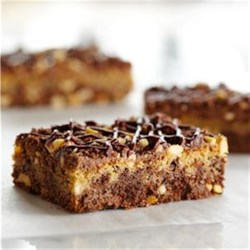 Buckeye Cookie Bars Recipe - A rich chocolate base layer is spread with a creamy peanut butter and chocolate layer, then baked and drizzled with chocolate fudge frosting.