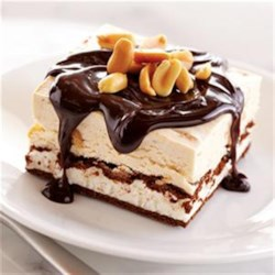 Chocolate Peanut Butter Ice Cream Sandwich Dessert Recipe - Whipped cream mixed with sweetened condensed milk and crunchy peanut butter is spread on a base of ice cream sandwiches, frozen, and served in squares topped with hot fudge and peanuts.
