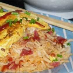 Omuraisu (Japanese Rice Omelet) Recipe - Omuraisu is a Japanese-style omelet made with fried rice. In this version, an egg omelet is draped over ham fried rice flavored with ketchup.