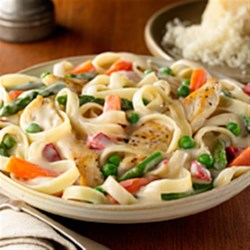 Chicken 'N Pasta Primavera Recipe - Sliced chicken breast and a blend of veggies are simmered until just done in a creamy Alfredo sauce with fettuccine.