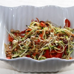 Raw Pad Thai Recipe - This colorful raw pad Thai uses zucchini strips as noodles and is coated in an almond butter-based sauce.