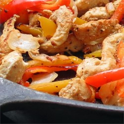 Swanny's Killer Fajitas Recipe - Delicious lime-marinated chicken and vegetables are folded into hot corn tortillas and served with fresh lettuce, tomato, and sour cream. Add your favorite toppings like taco sauce, guacamole, and a sprinkle of fresh cilantro if you like.