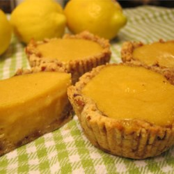 Paleo Lemon Tarts Recipe - These lemon tarts have a crust of ground almonds sweetened with dates and a tangy, honey-sweetened filling. They make a zingy and delicious paleo-style treat.