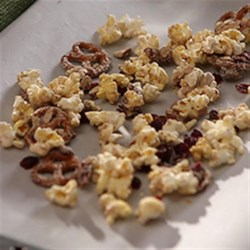 Ashley and Whitney's Popcorn and Pretzel Sweet Snack Mix Recipe - Your favorite snacks (popcorn, nuts, pretzels, dried cranberries) are tossed with melted white chocolate for this easy party mix.