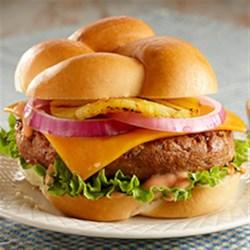 Hawaiian Burgers Recipe - Grilled turkey burgers are served on toasted buns with slices of Cheddar cheese, red onion, and grilled pineapple.