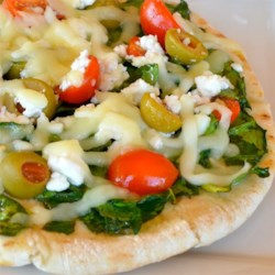 Individual Greek Pita Pizzas Recipe - Pita bread is topped with a Greek-inspired spinach salad with olives, feta cheese, and mozzarella cheese. A lemony dressing completes this vegetarian pizza.