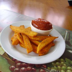Savory Sweet Potato Fries Recipe - Baked sweet potato wedges are tossed in a rosemary and olive oil blend creating a colorful and tasty side dish.