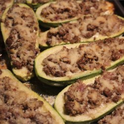 Stuffed Zucchini Boats with Meat Recipe - Zucchini halves are filled with ground chicken and provolone cheese, then topped with Parmesan cheese creating stuffed zucchini boats the whole family will love.