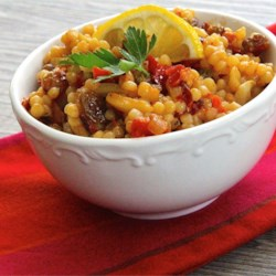Quick Moroccan Couscous Recipe - This Moroccan couscous has a perfect balance of sweet and savory from golden raisins, sun-dried tomatoes, and almonds and complements chicken quite nicely.
