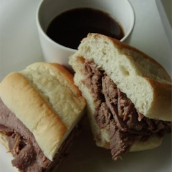 Easy Slow Cooker French Dip Recipe - For an easy French dip sandwich, this slow cooker French dip recipe uses rump roast slowly simmered in beef broth, onion soup, and beer.