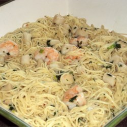 Savory Sea Scallops and Angel Hair Pasta Recipe - Lightly-cooked and tender sea scallops, served in the simplest, quickest sauce of lemon juice, butter, parsley, and fresh basil, are served over angel hair pasta for an elegant but easy dish. Add cream or Parmesan cheese if you like.
