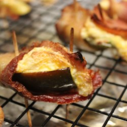Bluezy's Stuffed Jalapenos with Bacon Recipe - Jalapeno pepper halves are stuffed with creamy Cheddar cheese filling and topped with a bacon slice for a delicious warm appetizer with a hint of the heat. They're great on the grill, too.