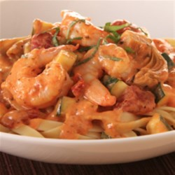 KRAFT RECIPE MAKERS Shrimp with Creamy Tomato Sauce Recipe - Shrimp, zucchini, and artichoke hearts are simmered in a creamy, cheesy sauce, served with fettuccine, and topped with fresh basil.