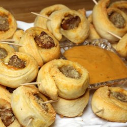 Easy Sausage Biscuit Bites Recipe - Sausage links are rolled in biscuit dough, topped with Parmesan cheese, and baked into tasty bites perfect for party appetizers.