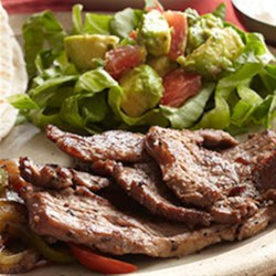 Bison Fajitas with Guacamole Salad Recipe - Strips of bison flank steak are quickly stir-fried with bell peppers, onion, and jalapeno and served hot on tortillas with salsa, sour cream, and guacamole.