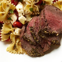 Caprese Bison Sirloin Steak with Bow Tie Pasta Recipe - The delicious flavor of freshly cooked bison steaks pairs beautifully with traditional Italian caprese ingredients like basil pesto, fresh mozzarella cheese, and sweet grape tomatoes.