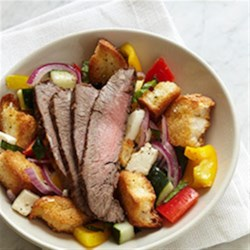 Panzanella Salad with Bison Flank Steak Recipe - Flavorful grilled bison flank steak is sliced thinly across the grain for maximum tenderness and served with an Italian-inspired toasted bread salad with tomatoes, fresh mozzarella cheese, and basil leaves.