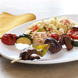 Sea-and-Shore Bison Kabobs with Mediterranean Couscous Salad Recipe - Colorful skewers of bison sirloin steak, tender sea scallops, mushrooms, zucchini, and cherry tomatoes are grilled and served with a Greek-inspired couscous salad in this gourmet recipe.