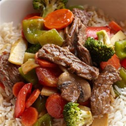 Sizzling Bison Steak Stir-Fry Recipe - Thinly sliced bison ribeye steaks and veggies are stir fried, mixed with an Asian-inspired ginger sauce, and served with hot brown rice.