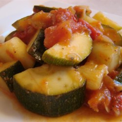 Tomato and Zucchini Melange Recipe - A nice side dish with practically no fat or calories that will go with any meal except a tomato-based one. If you like, you can add diced bell peppers to this dish too. Serve hot in a small dish.