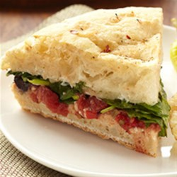 Stuffed Focaccia with Spinach, Tomatoes, Olives and Mozzarella Recipe - A split loaf of focaccia spread with seasonings, topped with chopped tomatoes, olives, veggies and cheese is baked until hot and cheese is melted for a delicious lunch or snack.