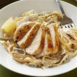 Lemon Linguine with Chicken, Beans and Artichokes Recipe - Browned, sliced chicken breasts are served atop linguine in a creamy cheese sauce with artichoke hearts and French-cut green beans.