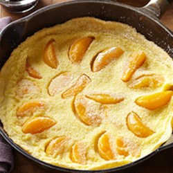 Peach Dutch Baby with Blueberry Compote Recipe - Your brunch will be the talk of the town when you serve a puffy pancake baked with sliced peaches and a sweet blueberry sauce. A bit of optional shredded sweet basil adds a touch of elegance. You can also serve this elegant dish for dessert.