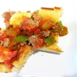Zucchini, Pork, and Peppers Recipe - Ground pork, zucchini, and peppers (sweet and hot) are cooked in the skillet (or use an electric frying pan) and served on slices of Italian bread. This makes a great appetizer or snack!
