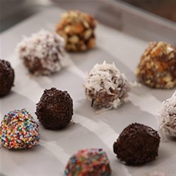 Utokia's Chocolate Peanut Butter Candies Recipe - Chocolate and peanut butter candies are rolled in chopped nuts, flaked coconut, or sprinkles--your choice--for these sweet little treats individually wrapped in parchment paper.