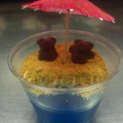 At the Beach Jell-O(R) Treat Recipe - Create a cute beach scene layering berry-flavored gelatin with graham cracker crumbs for the sand and bear-shaped graham cracker snacks for the beach-goers under a cocktail umbrella.