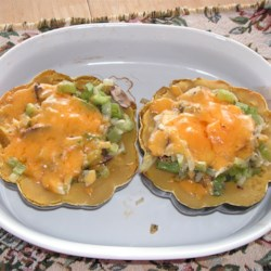 Cheesy Acorn Squash Recipe - Baked acorn squash filled with a saute of celery, onions and mushrooms, and topped with cheese.