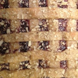 Linzer Cookies Recipe - This version of Linzer cookies are made as bars, not cutouts, but they taste just as good! The almond dough encases a filling made with dried apricots and apricot preserves.