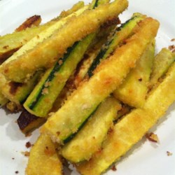 Oven Baked Zucchini Fries Recipe - Pieces of zucchini are dipped in butter and coated in seasoned breadcrumbs and Parmesan cheese then baked until golden brown and crunchy.