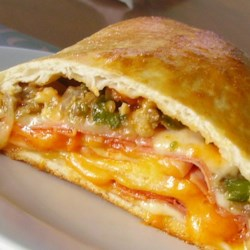 Man vs. Meat Stromboli Recipe - Get ready to feed a crowd with this meaty stromboli. With ground beef, salami, coppa ham, pepperoni, and plenty of mozzarella and provolone cheese, this calzone-like sandwich is sure to satisfy.