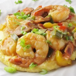 Old Charleston Style Shrimp and Grits Recipe - Tender shrimp and andouille sausage with red, green, and yellow bell peppers are served over cheese-flavored grits in this traditional low-country favorite.
