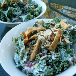 Creamy Kale Salad Recipe - A creamy dressing of yogurt, mayonnaise, and lemon juice coats kale, onion, and raisins in this salad recipe.