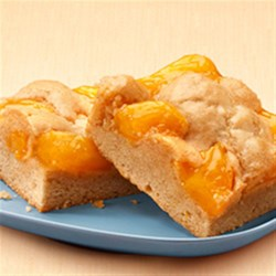 Just Peachy Pie Bars Recipe - Spiced peach pie filling baked on a buttery crust and dotted with more batter is served warm with a drizzle of glaze.