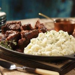 Braised Short Ribs with Roasted Garlic Horseradish Mashed Recipe - Beef short ribs are braised for hours with wine and vegetables in the oven until tender and flavorful, then served with horseradish mashed potatoes for a hearty meal perfect for cooler weather.