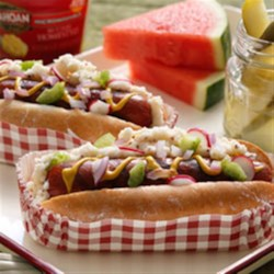 Idahoan(R) Picnic Dog Recipe - Grilled hot dogs on potato bread buns are topped with mashed potatoes with mustard and your choice of toppings.