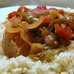 Saucy Slow Cooker Pork Chops Recipe - Pork chops are simmered in a slow cooker with a flavorful tomato-based sauce for a warm and filling dinner for the whole family.