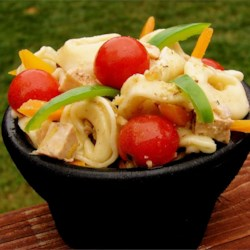 Charlotte's Tortellini Salad Recipe - Tender cheese tortellini, crunchy red and green bell pepper strips, cooked chicken breast, feta cheese, and black olives comprise this hearty Greek-style salad. It's topped with a tangy dressing made with olive oil, lemon zest, walnuts, and honey.