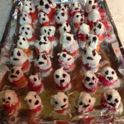 White Chocolate Strawberry Ghosts Recipe - White chocolate-dipped strawberries get a cute face thanks to a piping of melted semisweet chocolate for adorable Halloween ghost treats.