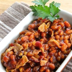 Apple Baked Beans Recipe - Add apples, bacon, and raisins to cans of pork and beans to bake a new version of baked beans everyone will love.