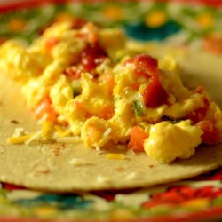 Tex-Mex Migas Recipe - Sprinkle crushed tortilla chips over spicy eggs and wrap in a tortilla with Cheddar cheese for a Tex-Mex breakfast favorite from central Texas.