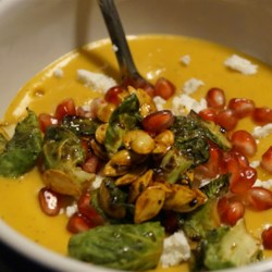 Smokey Butternut Squash Soup Recipe - Enjoy the spicy, smokey flavor of this butternut squash soup topped with pomegranate seeds, goat cheese, and crispy Brussels sprouts.